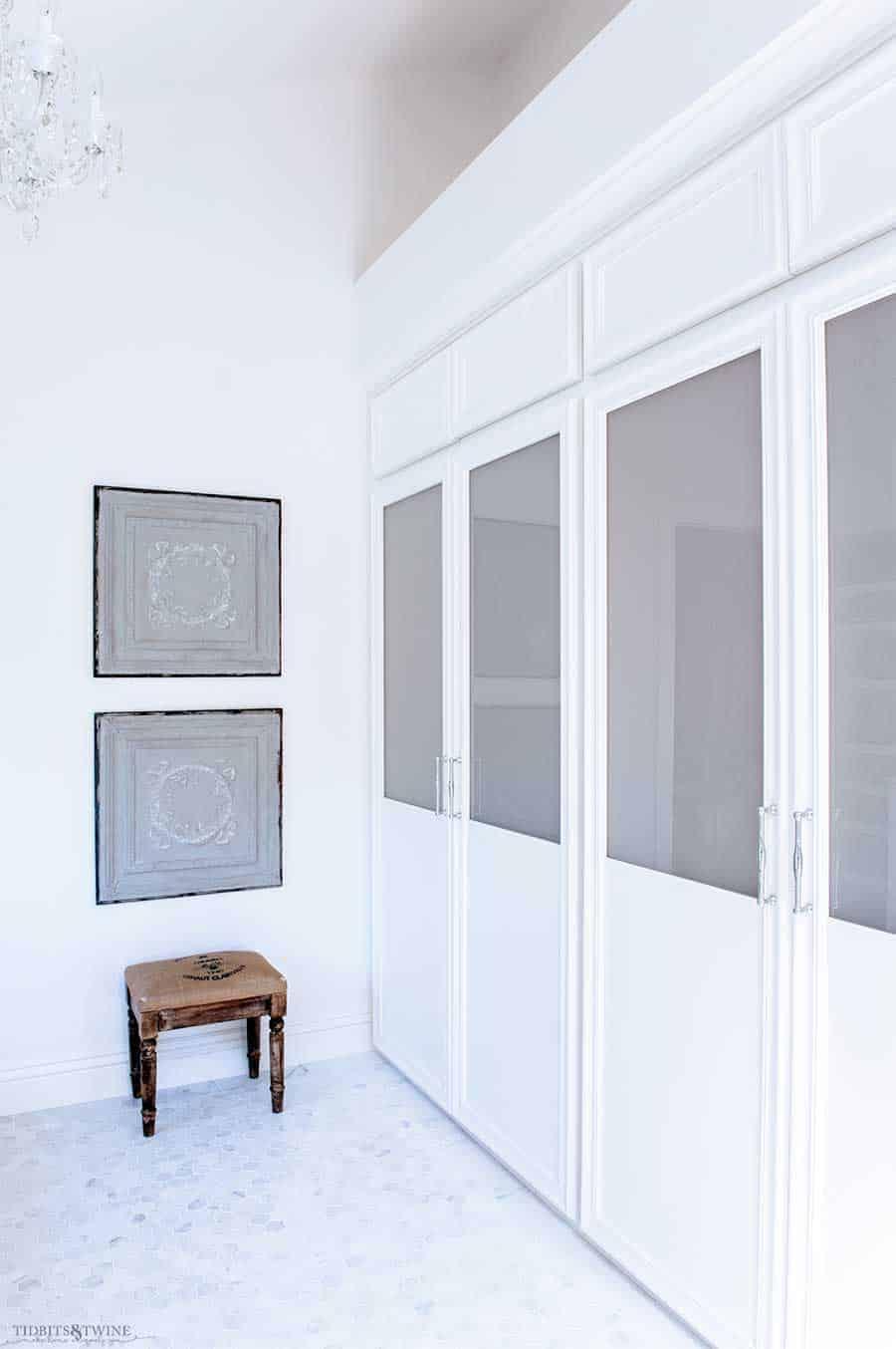 Ladrilho hexagonal branco em um banheiro com portas de armário de vidro fosco.