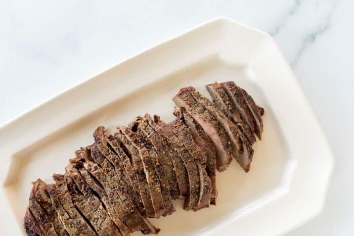 Broiled steak on a white platter, sliced into thin pieces.