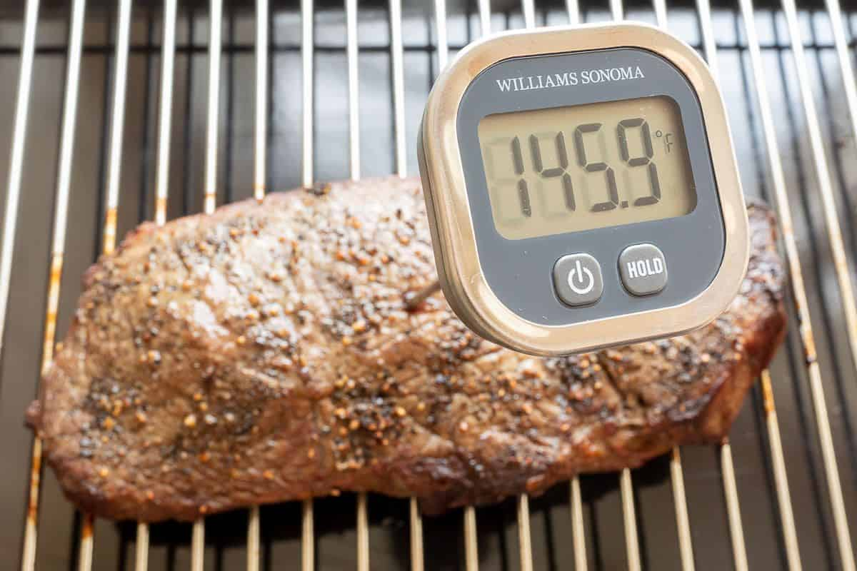 A piece of broiled steak on a broiling pan with a digital thermometer showing 145.9 degrees in a tutorial for how to broil steak.