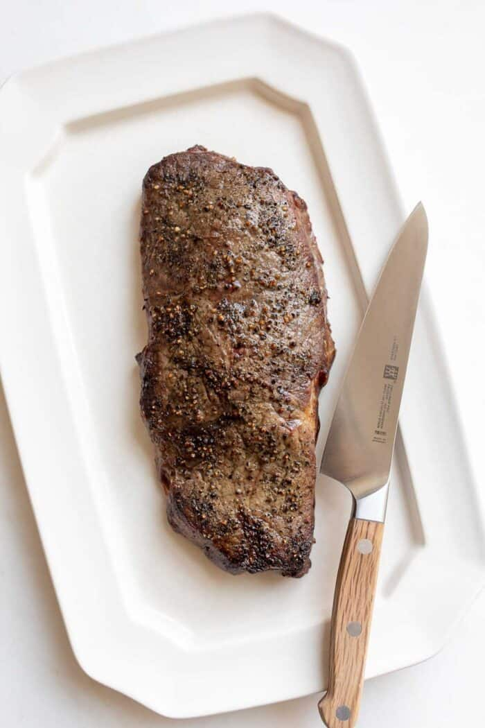 A broiled steak on a white platter, large knife to the side.