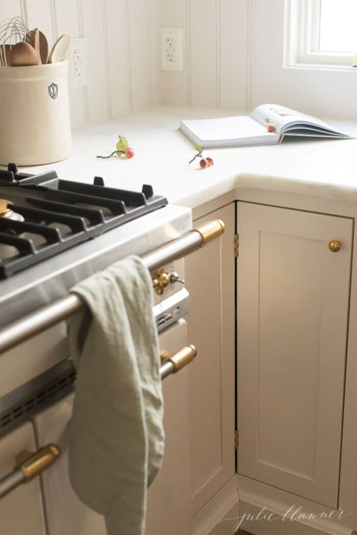 Cream kitchen cabinets topped with a marble eased edge countertop.