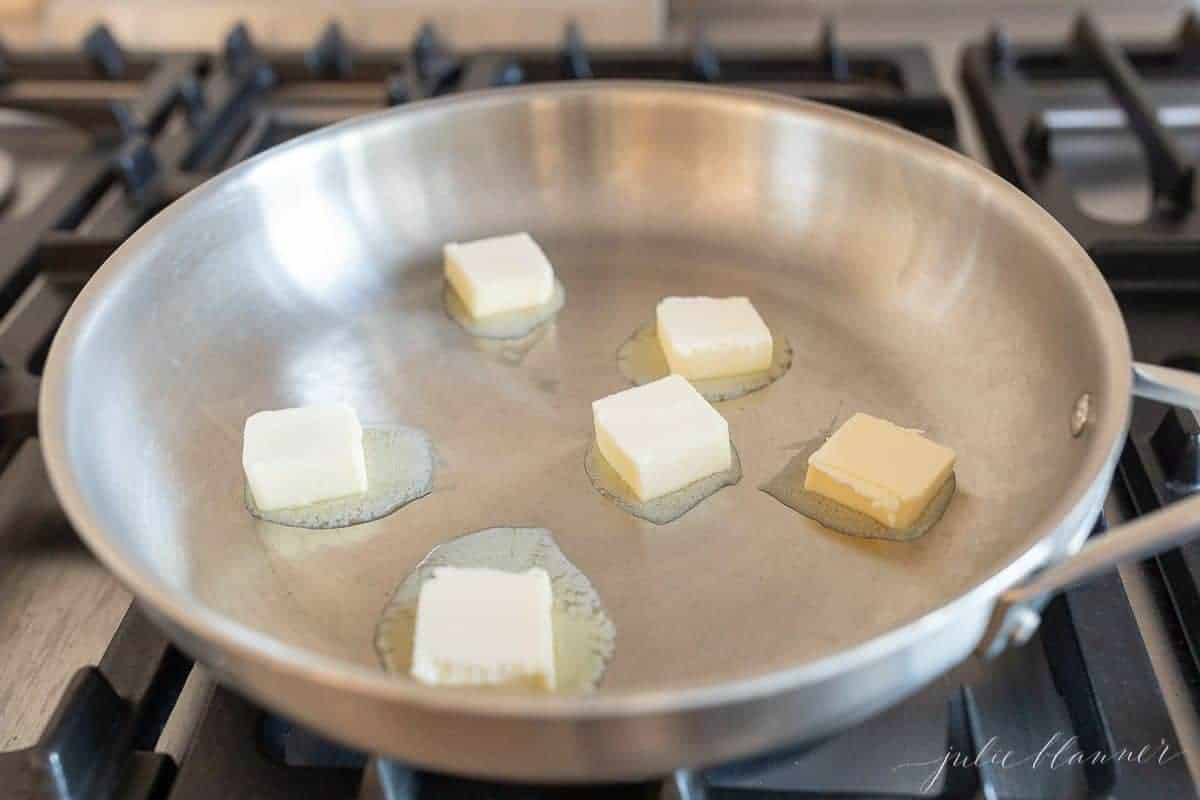A silver pan on a stovetop, filled with melting pats of butter.