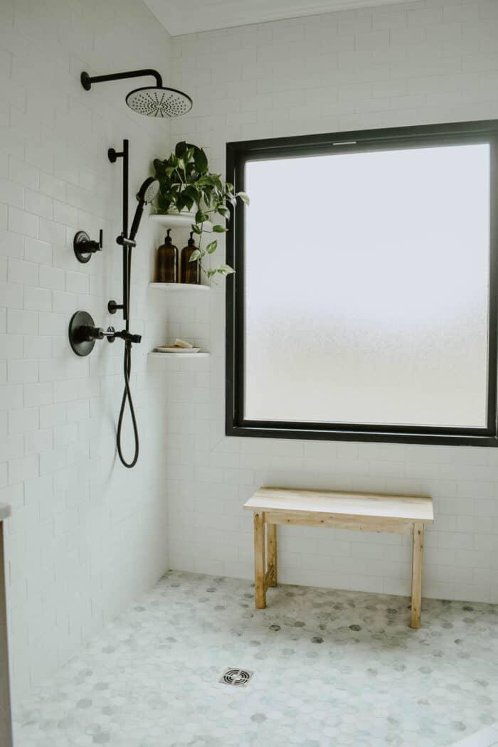 Um banheiro branco com uma banheira moderna e piso de ladrilho hexagonal.