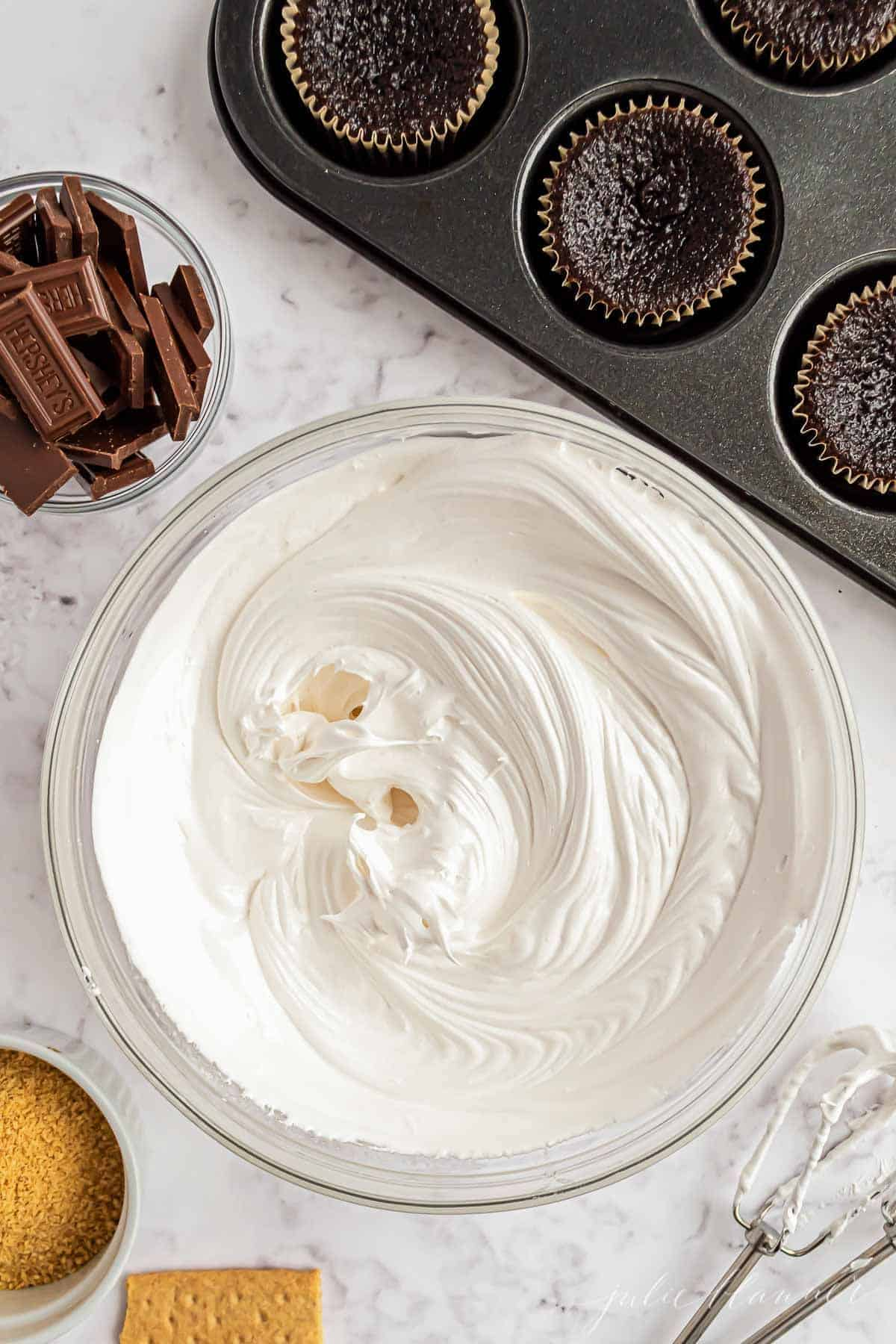 A clear glass bowl full of marshmallow icing, near chocolate cupcakes.