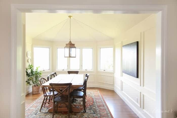 A white dining room with a brass lantern and box molding on the walls.