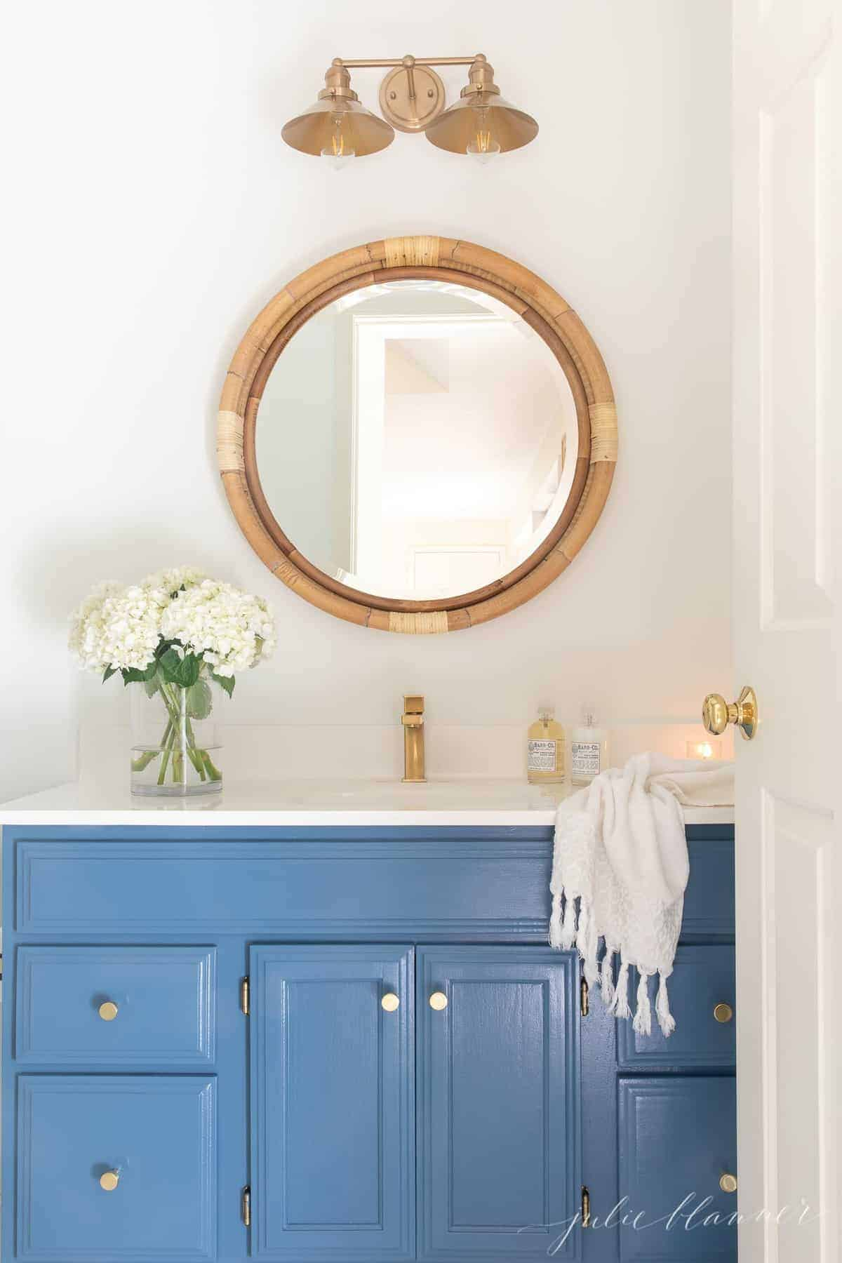 A nautical bathroom with a blue vanity and a round mirror.