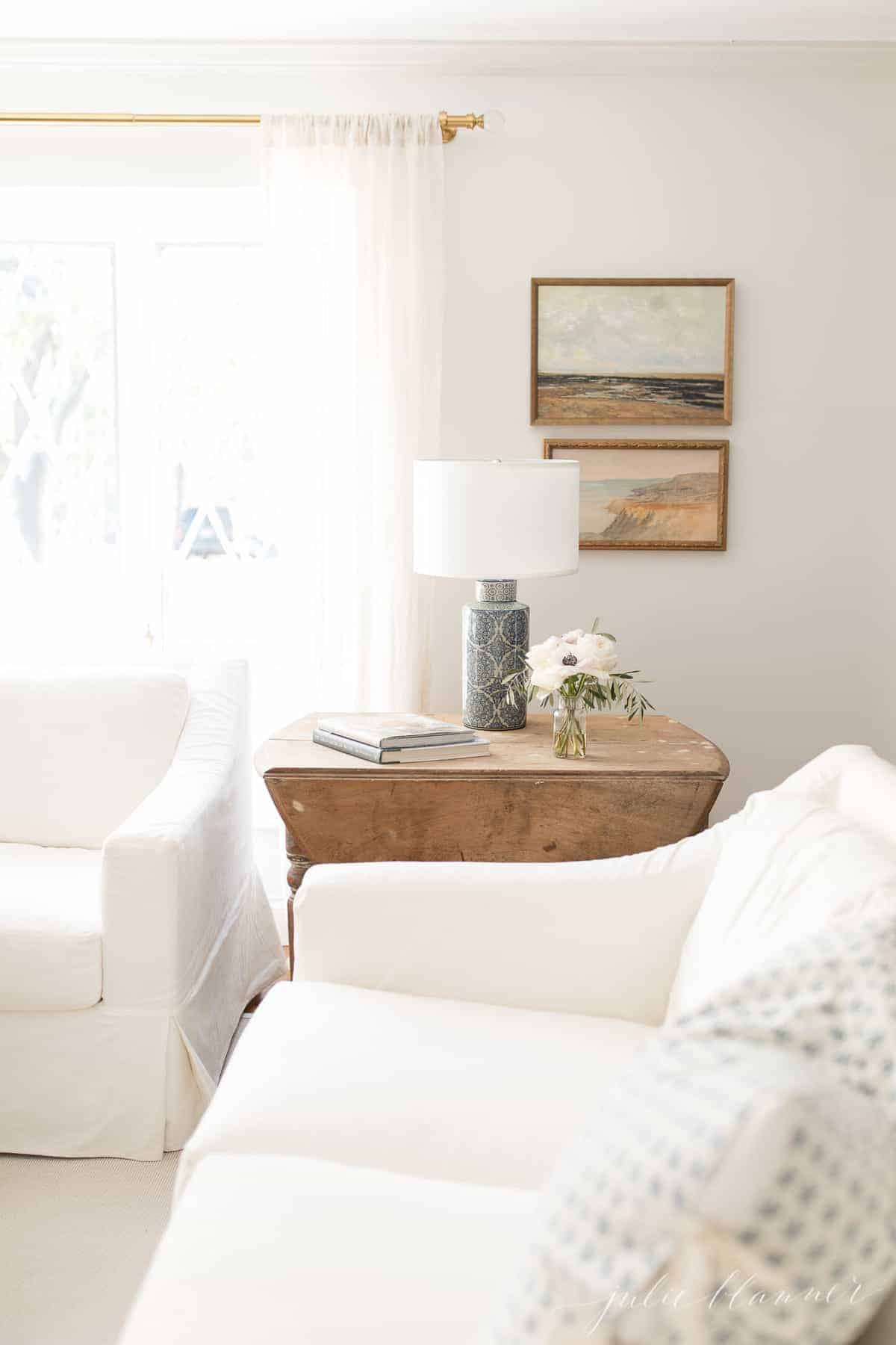A living room with white sofas and white walls, with a wood accent table and framed public domain Studio McGee art.