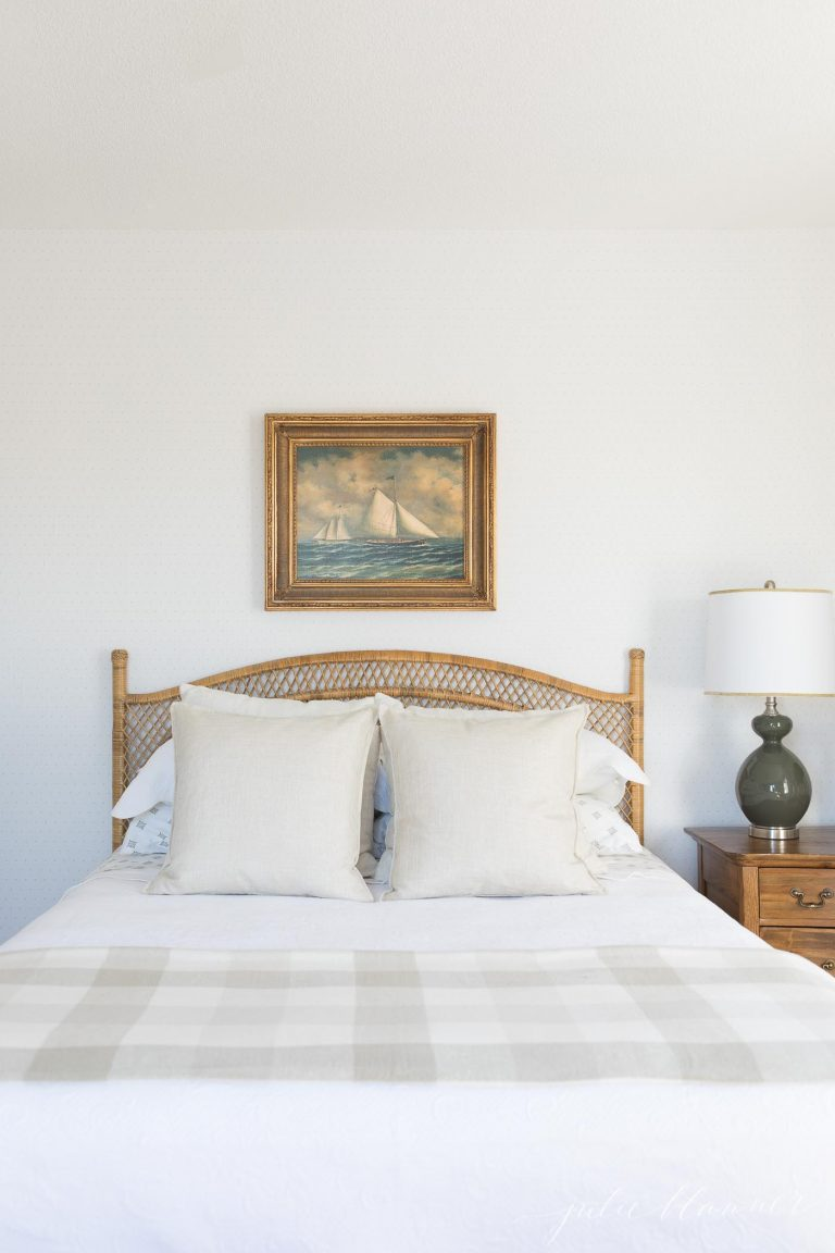 A bedroom with a rattan headboard and a piece of free public domain art above the bed.