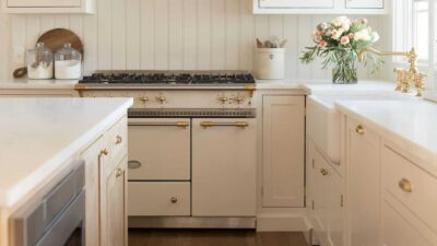 A white kitchen with shaker cabinets and marble counters, with a vase of flowers by the sink.