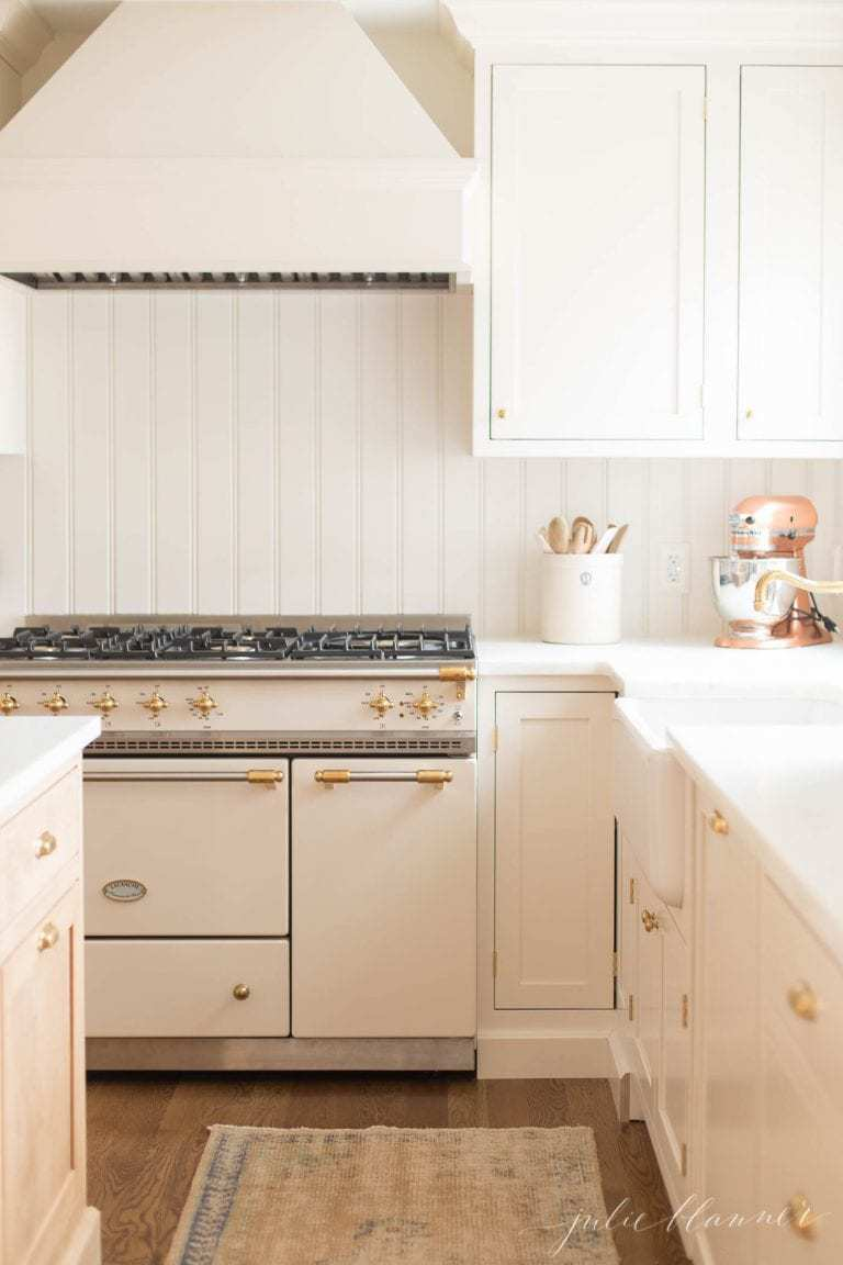 A white kitchen with shaker cabinet doors and marble counters, and fall branches in the sink.