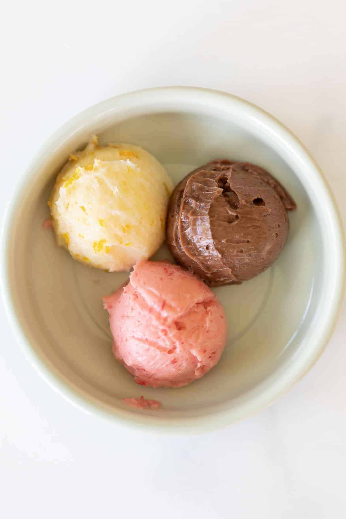A white bowl full three scoops of flavored butters, one orange, one chocolate and one strawberry.