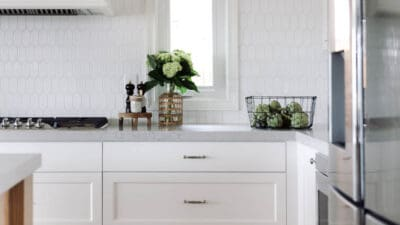A kitchen with white hexagon tile backsplash and white cabinets.
