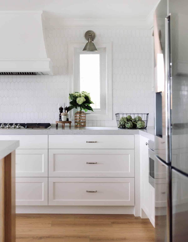Uma cozinha com backsplash de telha hexagonal branca e armários brancos.