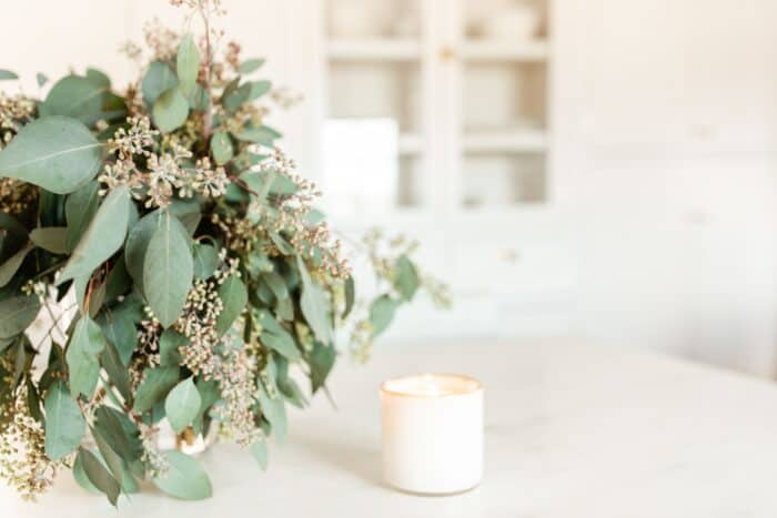 A vase of fresh eucalyptus on a marble island, white candle nearby.