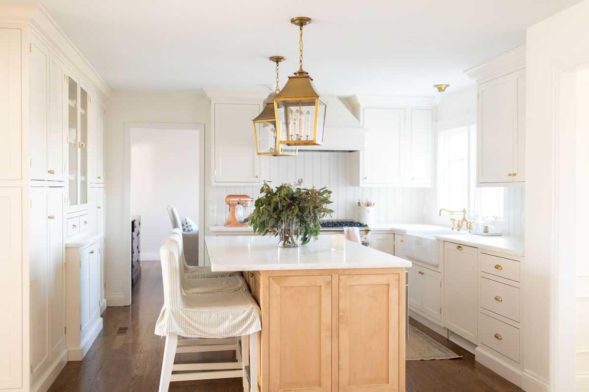 A white kitchen with a wooden island, vase of fresh eucalyptus on the island under lanterns.