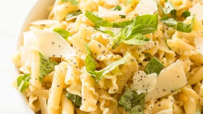 pasta salad topped with basil parmesan and pine nuts