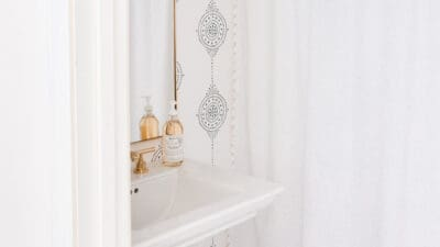 white and navy wallpapered bathroom with tassel shower curtain