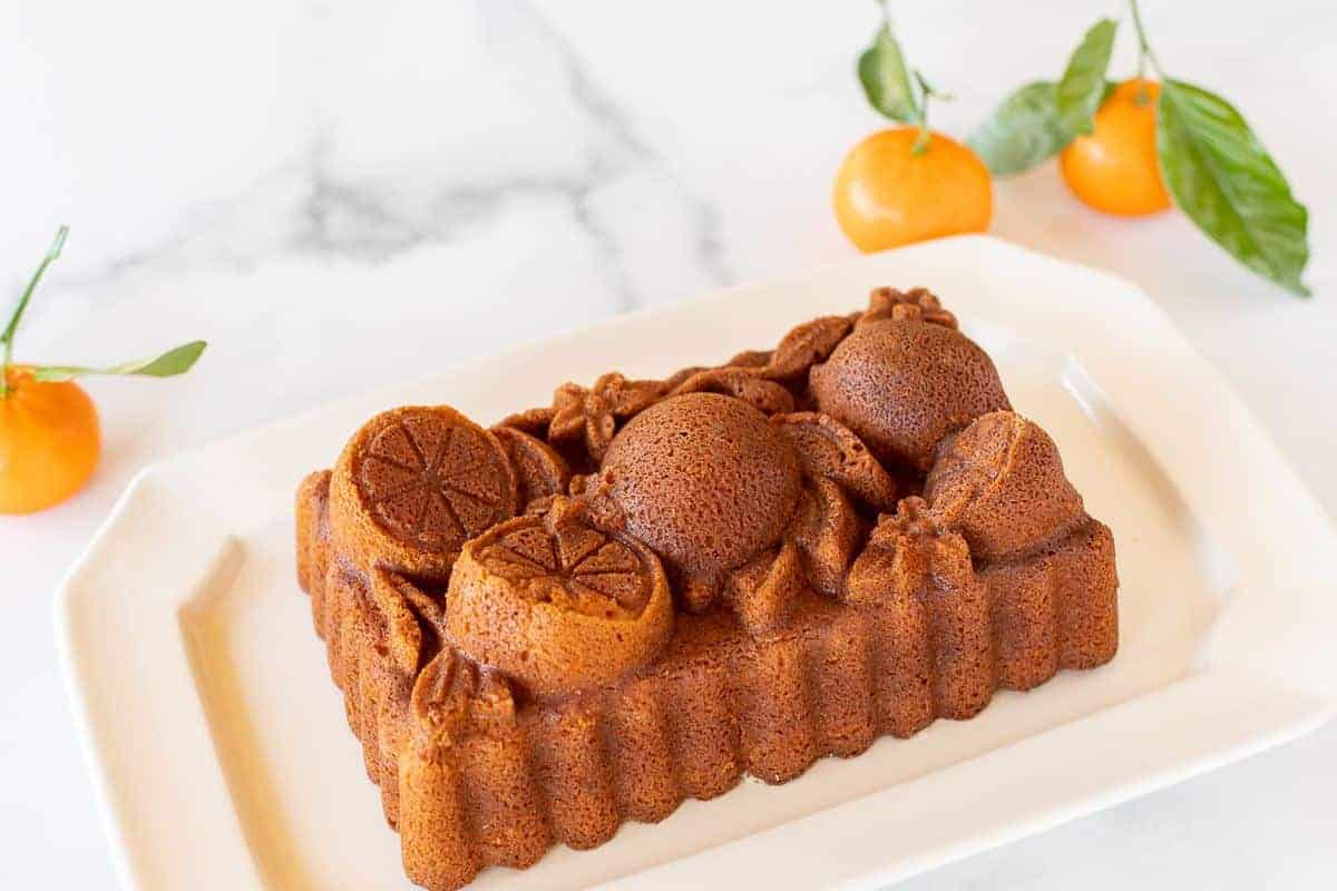 An orange pound cake from a citrus loaf pan, on a white platter. Oranges in the background.