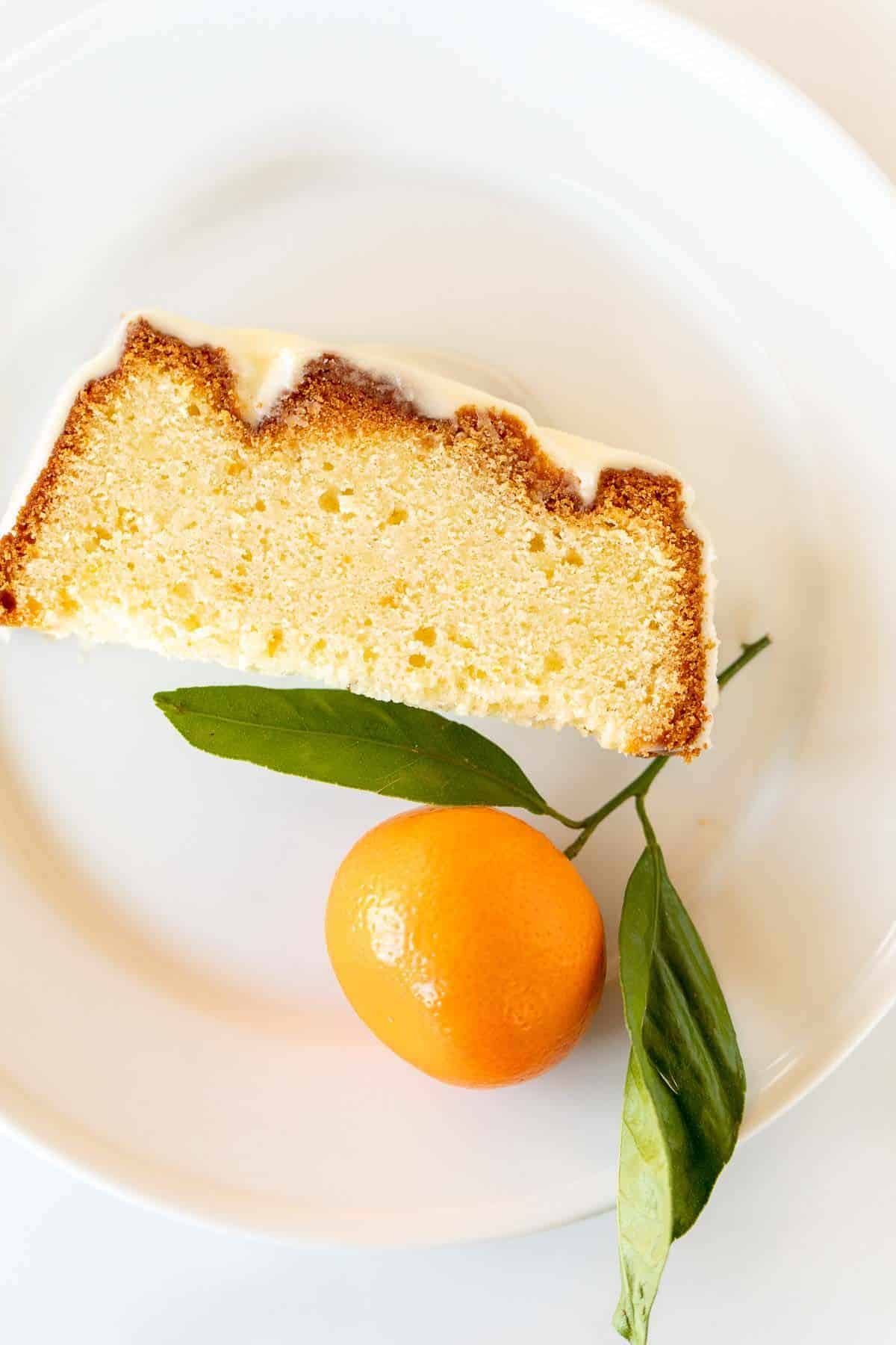 A single slice of orange pound cake on a white plate, single orange to the side.