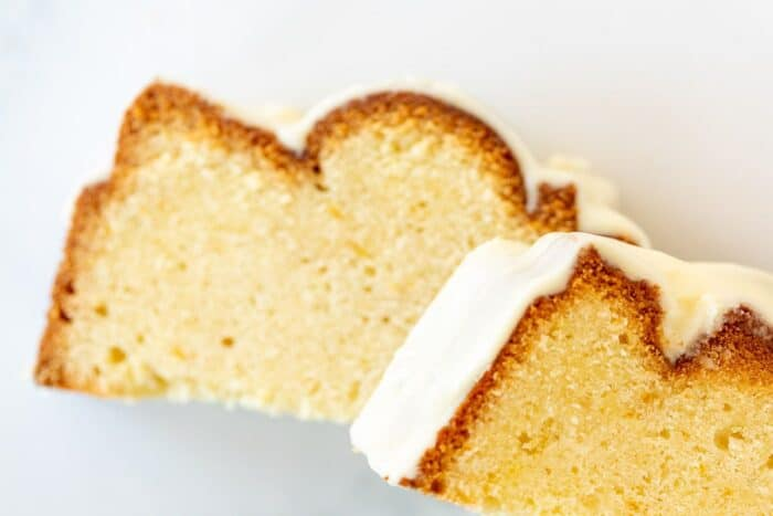 Two slices of orange pound cake topped with frosting on a white surface.