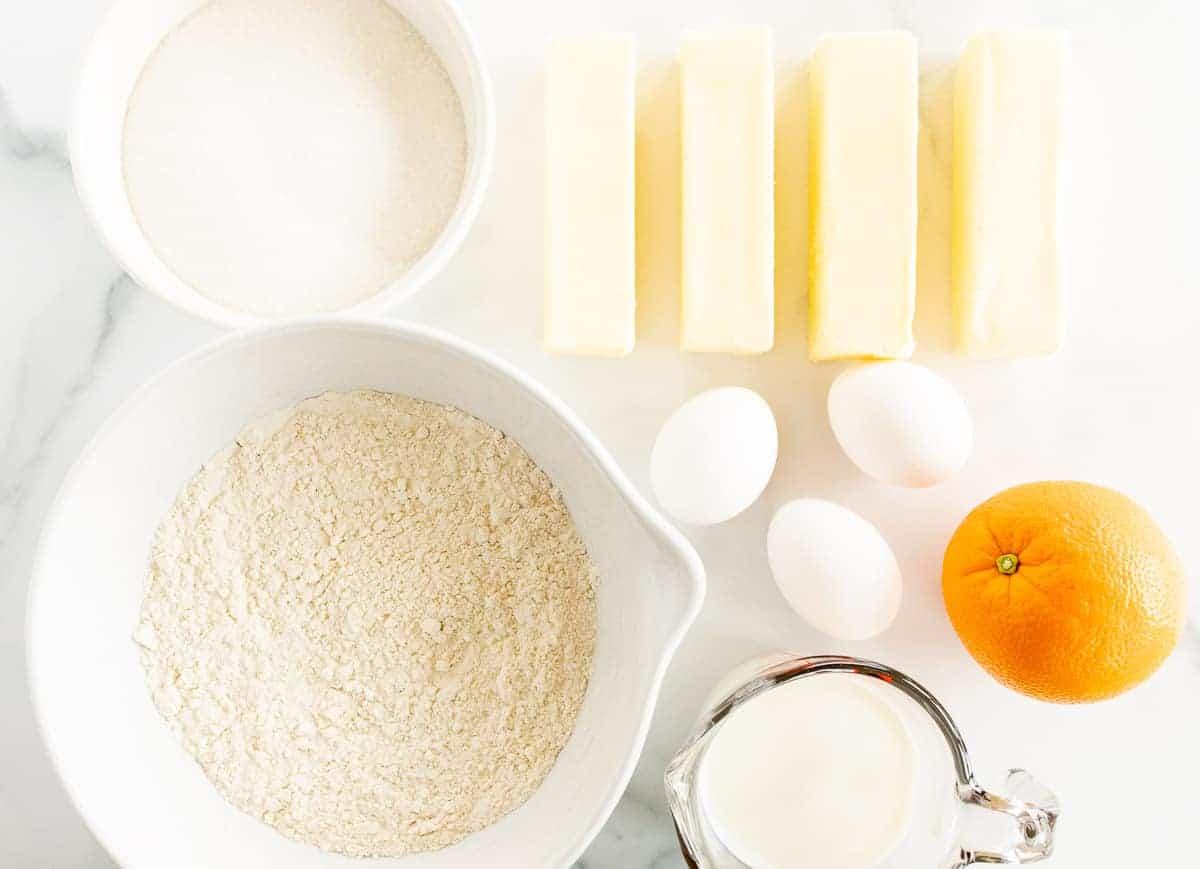 ingredients to make orange pound cake on white surface