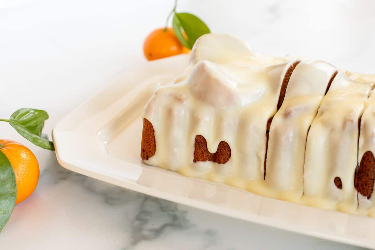 An orange pound cake covered in frosting on a white platter, oranges in the background.