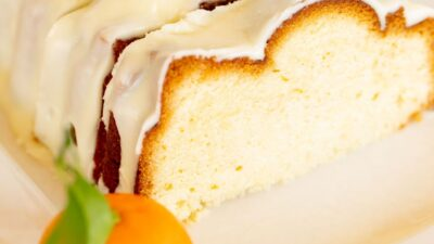 A sliced orange pound cake covered in frosting on a white platter, oranges in the background.