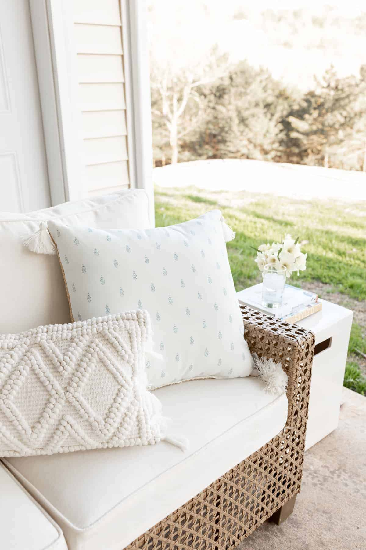 An outdoor room patio scene with a white sectional and flowers on a side table.