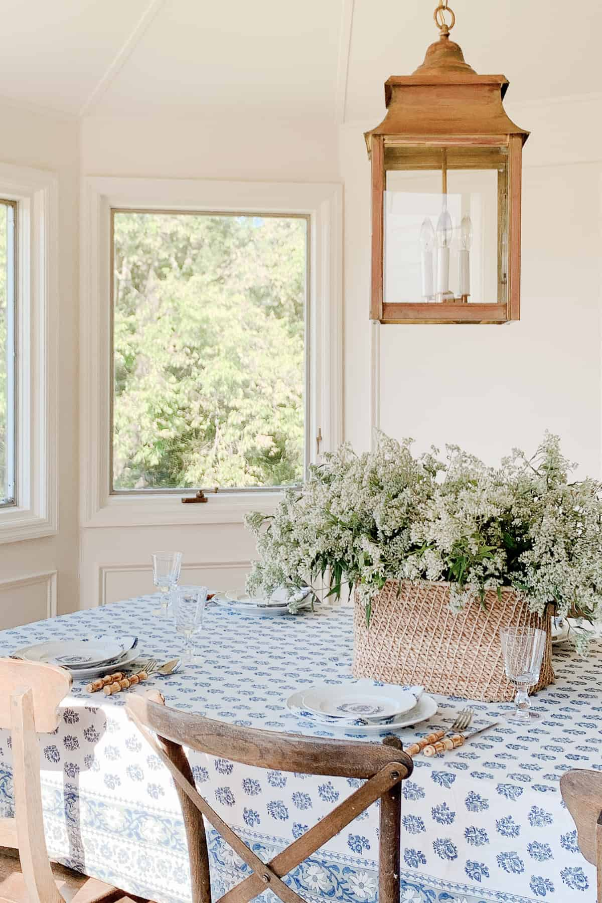 breakfast room with basket of flowers and block print table cloth