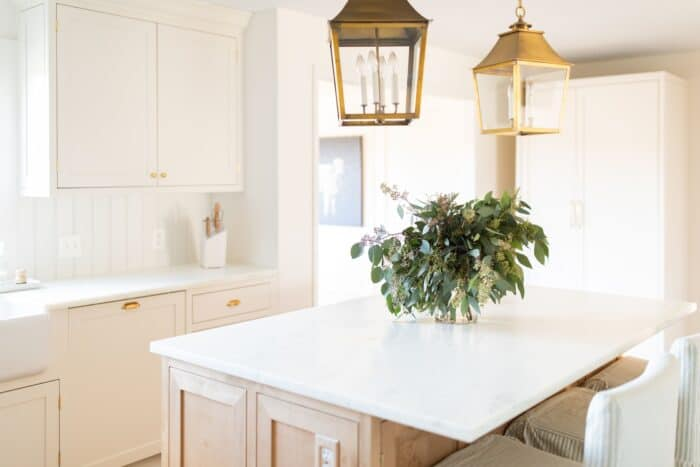 A cream kitchen with a vase of seeded eucalyptus on the island.