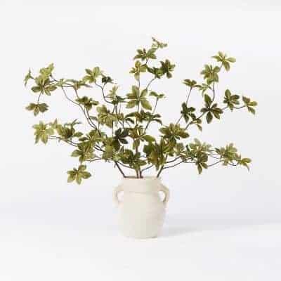 A faux greenery arrangement in a white ceramic vase