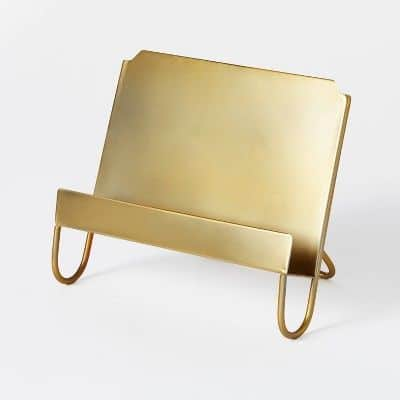 A gold cookbook stand on a white surface
