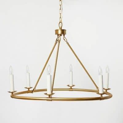 A circular brass chandelier on white background