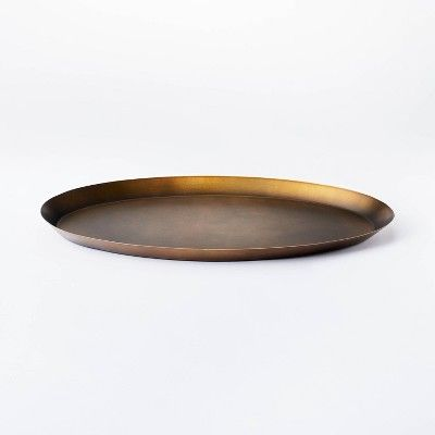 An oval gold metal tray on a white background