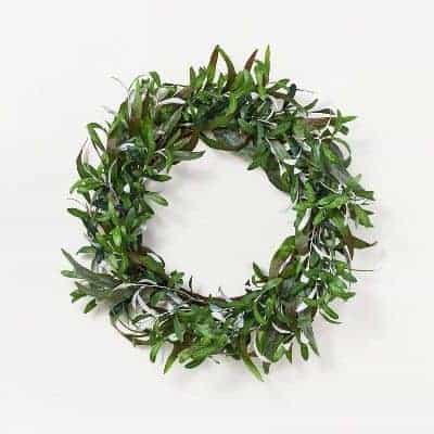 A faux olive branch wreath on a white surface