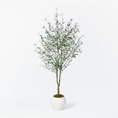 A large faux olive tree in a white pot on a white background, from studio mcgee for target