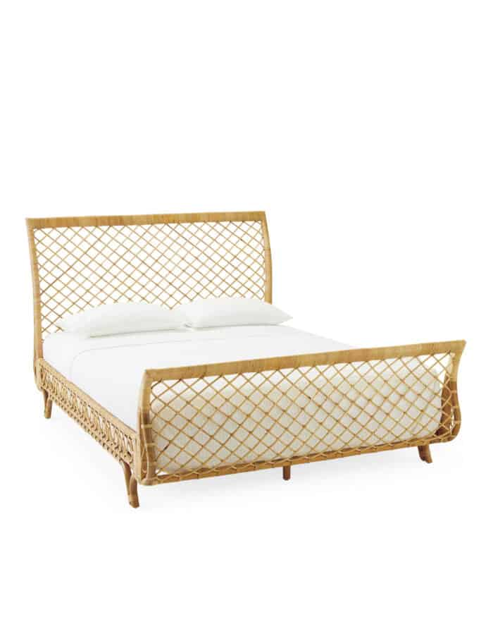 A king size rattan bed with headboard and footboard and white bedding.