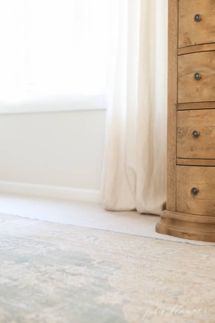 A soft blue rug over carpet in a bedroom, wood dresser and window in background.