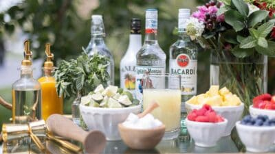 An at-home mojito bar cart with a variety of the best rums for mojitos in the background.