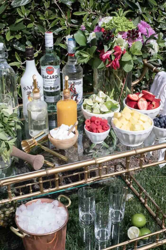 A mojito bar cart at home with a variety of the best mojito rums in the background.