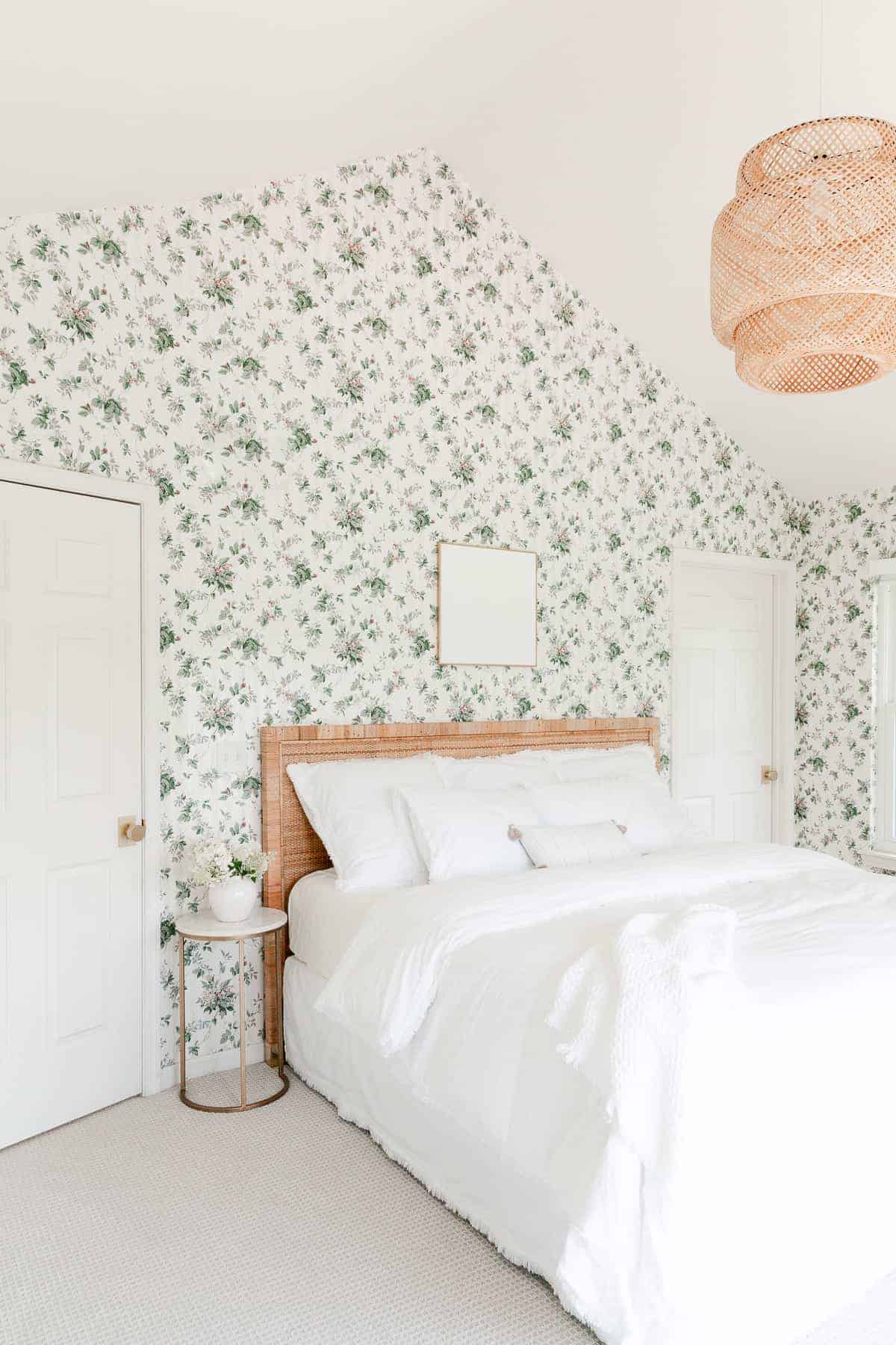 ikea pendant light over rattan bed with white bedding in wallpaper bedroom