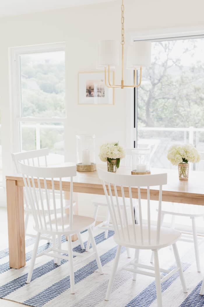 teak dining table with white chairs and blue stripe rug