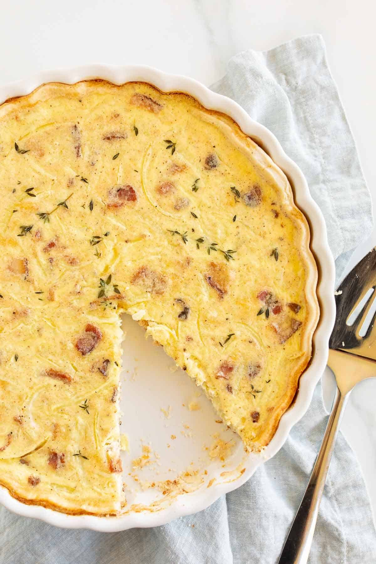 A quiche with one slice removed, pie server to the side.