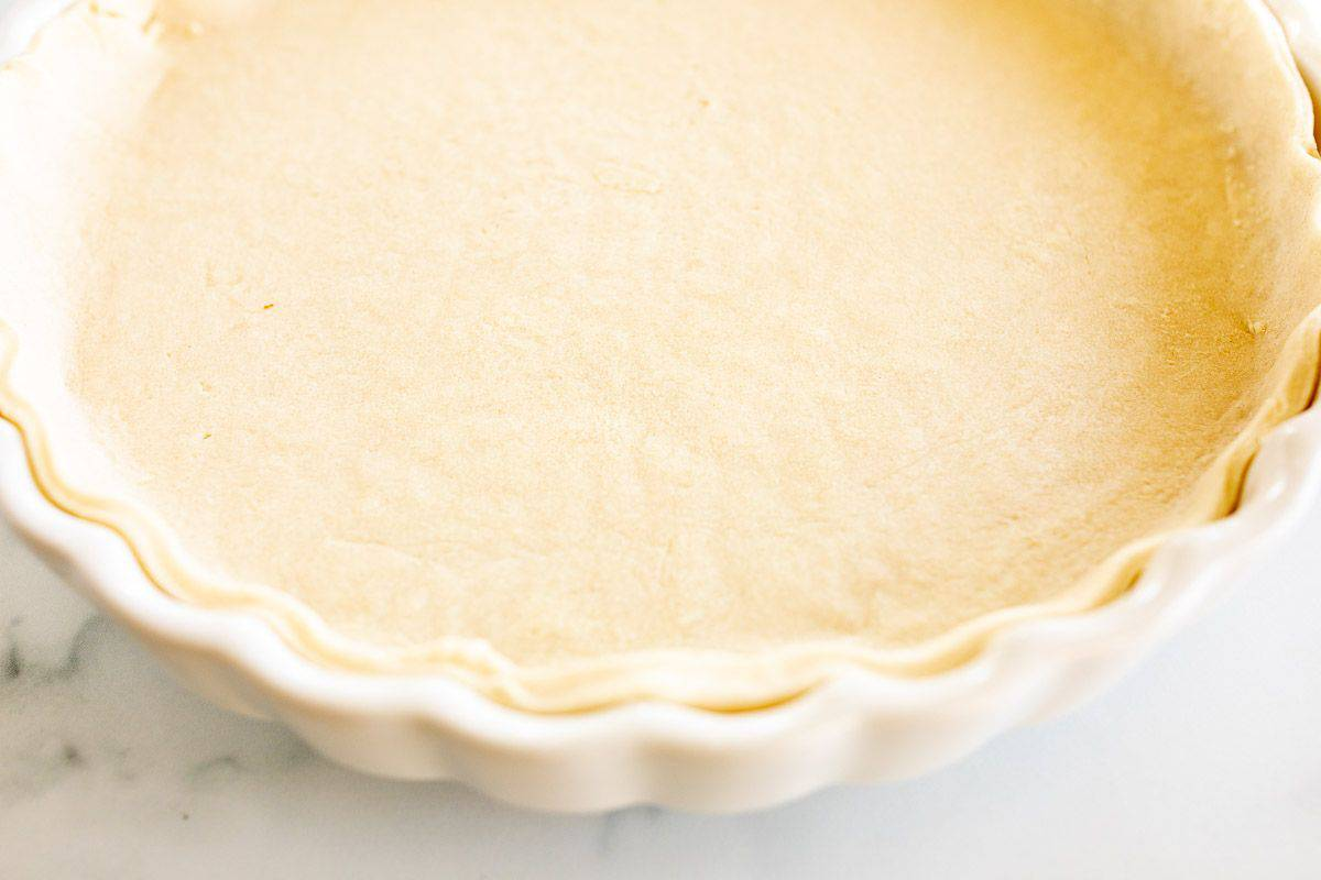 An unbaked pie crust in a white pie dish on a marble surface.