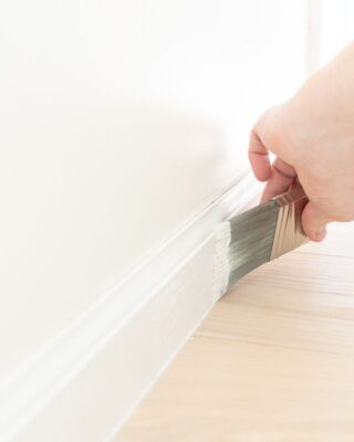 A hand painting trim white with a brush, next to a light wood floor.