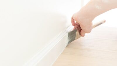 A trim of white hand paint with a brush, next to a light wood floor.
