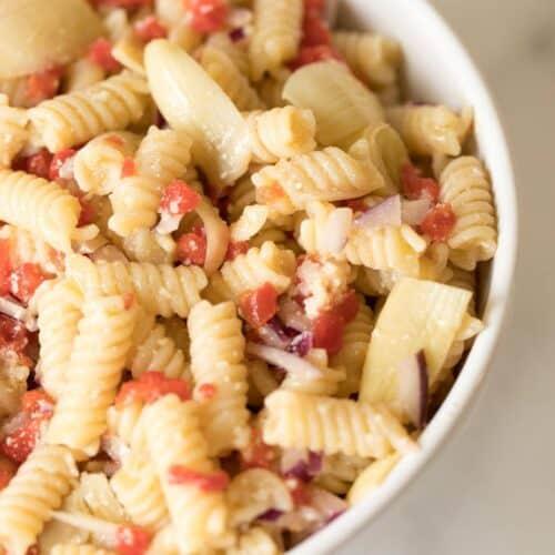 An italian pasta salad recipe in a white bowl