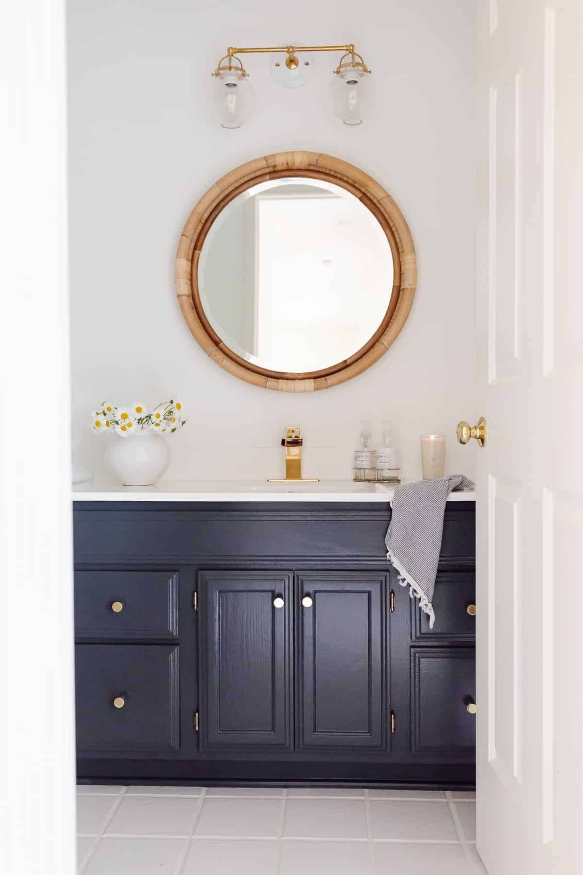 blue and white bathroom with rattan mirror and brass hardware