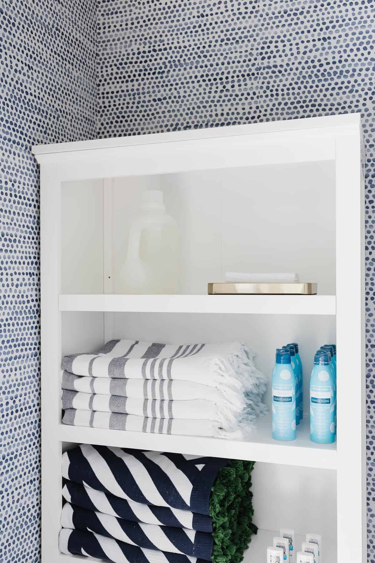 bookcase inside of closet boasting laundry detergent dryer sheets and towels
