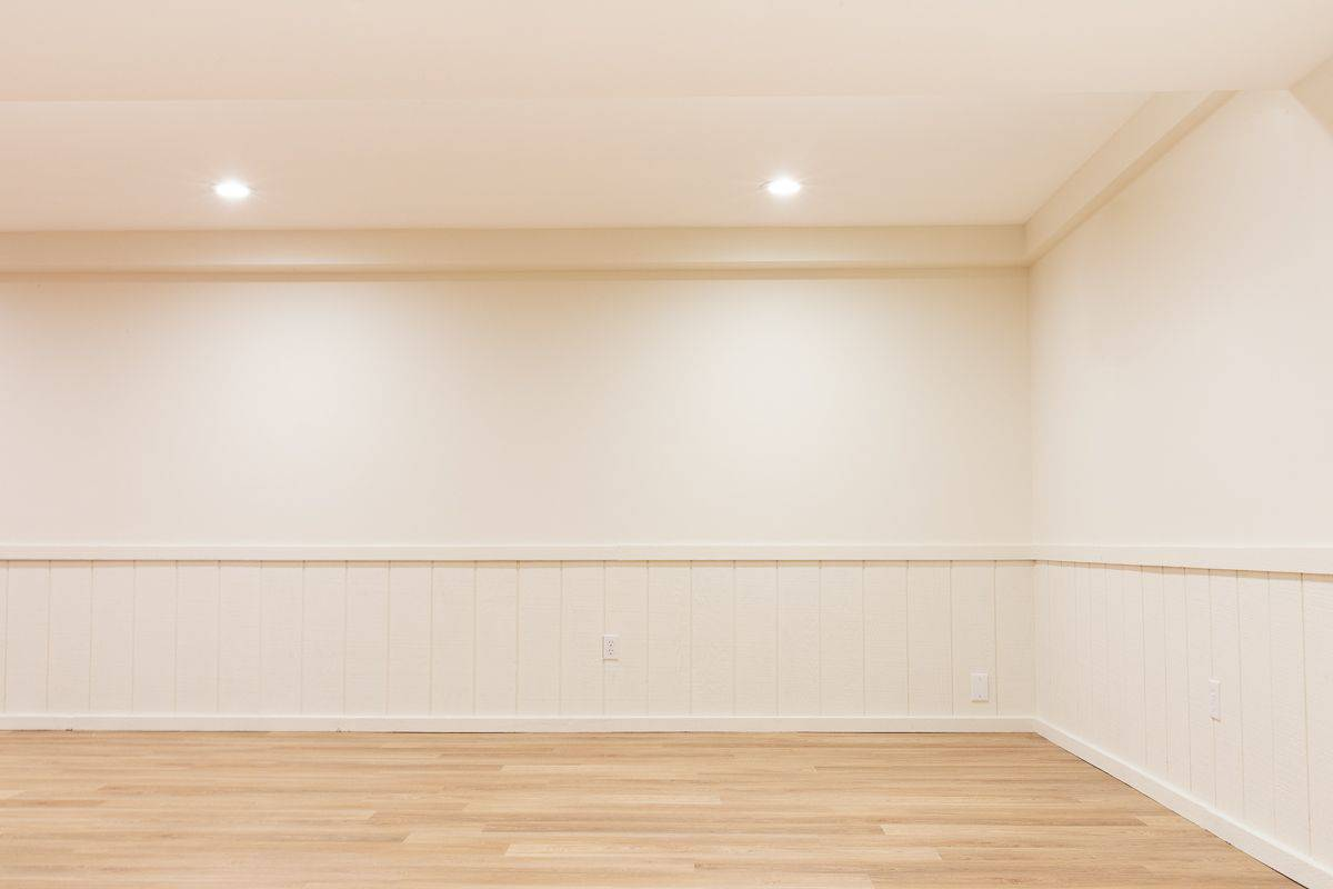 An empty basement with white walls and a medium toned vinyl plank flooring.